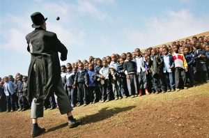 A clown performs to a crowd of refugees
