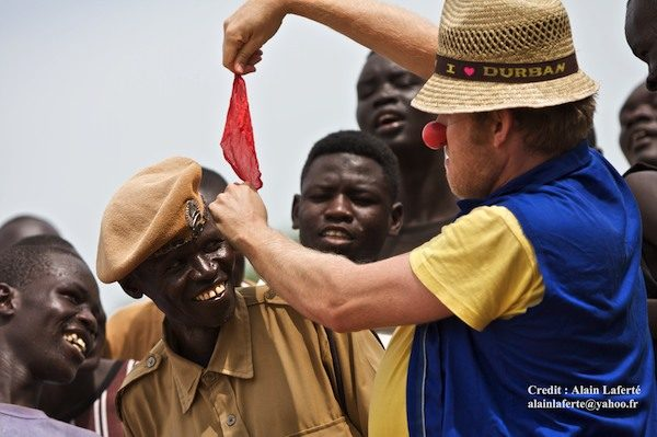 Male clown pulls a red scarf out of a official's ear. People look on and smile.