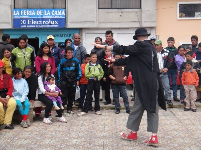A clown performs in a city square. He is doing hat tricks for the audience.
