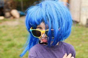 Girl in a blue wig and over-sized sunglasses. Spring Fling fun-raising.