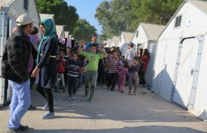 Clay Mazing leads a clown parade of displaced children through a refugee camp, Lesvos, Greece.