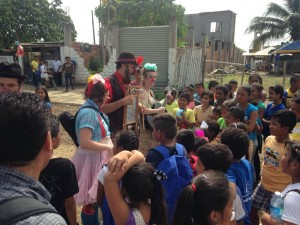 Four clowns stand and play instruments to a large group of children on a dirt road in a damaged part of Ecuador.