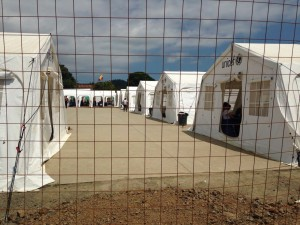 Looking inside the camp, past the tall fence, is a refugee camp with long rows of white, sterile shelters.