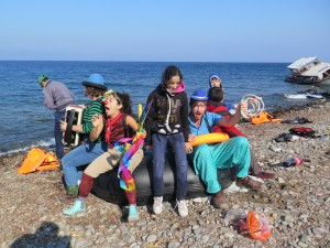 Young girl bounces with clowns on large life raft on rocky beach of Lesvos island. pictures.