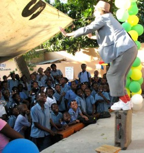 Clown balances on a standing suitcase before a large crowd of children. A case for clowns, ebola.