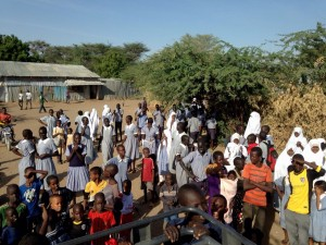 Kakuma refugee camp. Large crowd of children and adults surround the truck that brings in the clowns for a performance.
