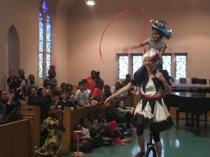 Bekah carries Masa on her shoulders as they run through the church waving streamers and laughing; from the Thanksgiving feast performance