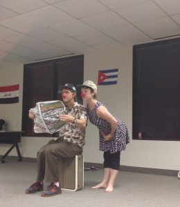 Clown David sits on a suitcase reading a newspaper looking annoyed as clown Becky intrusively reads the paper over his shoulder