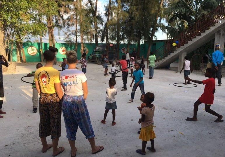 Two female clowns watch kiddos hula hoop