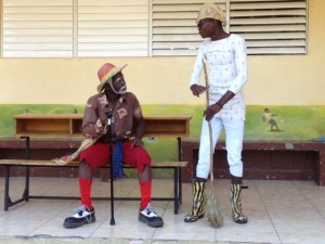 Two Haitian men perform an outdoor skit