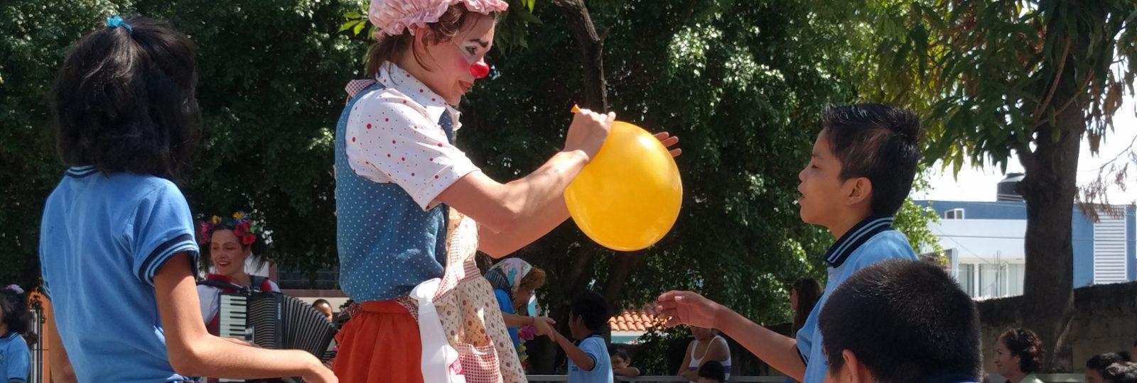 A clown ties off a balloon for a little boy