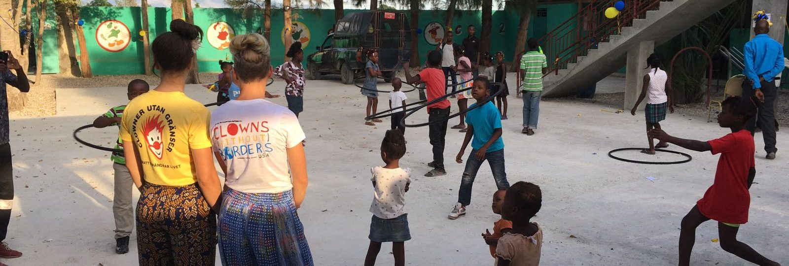 Clowns watch children play with hula hoops
