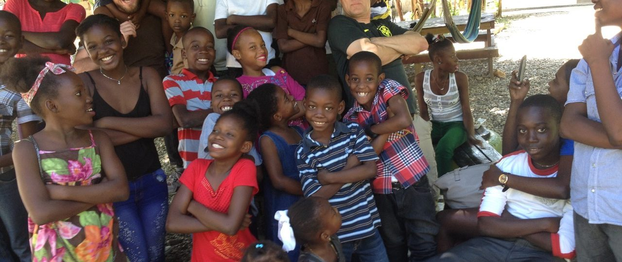 Clowns pose under a tree in Haiti