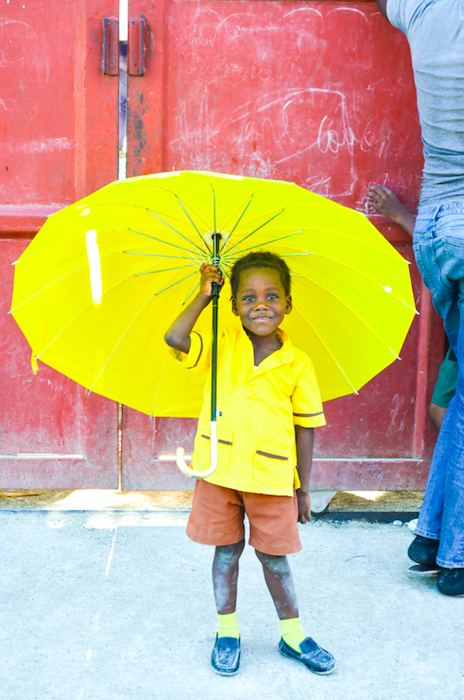 A little boy holds a big yellow umbrella