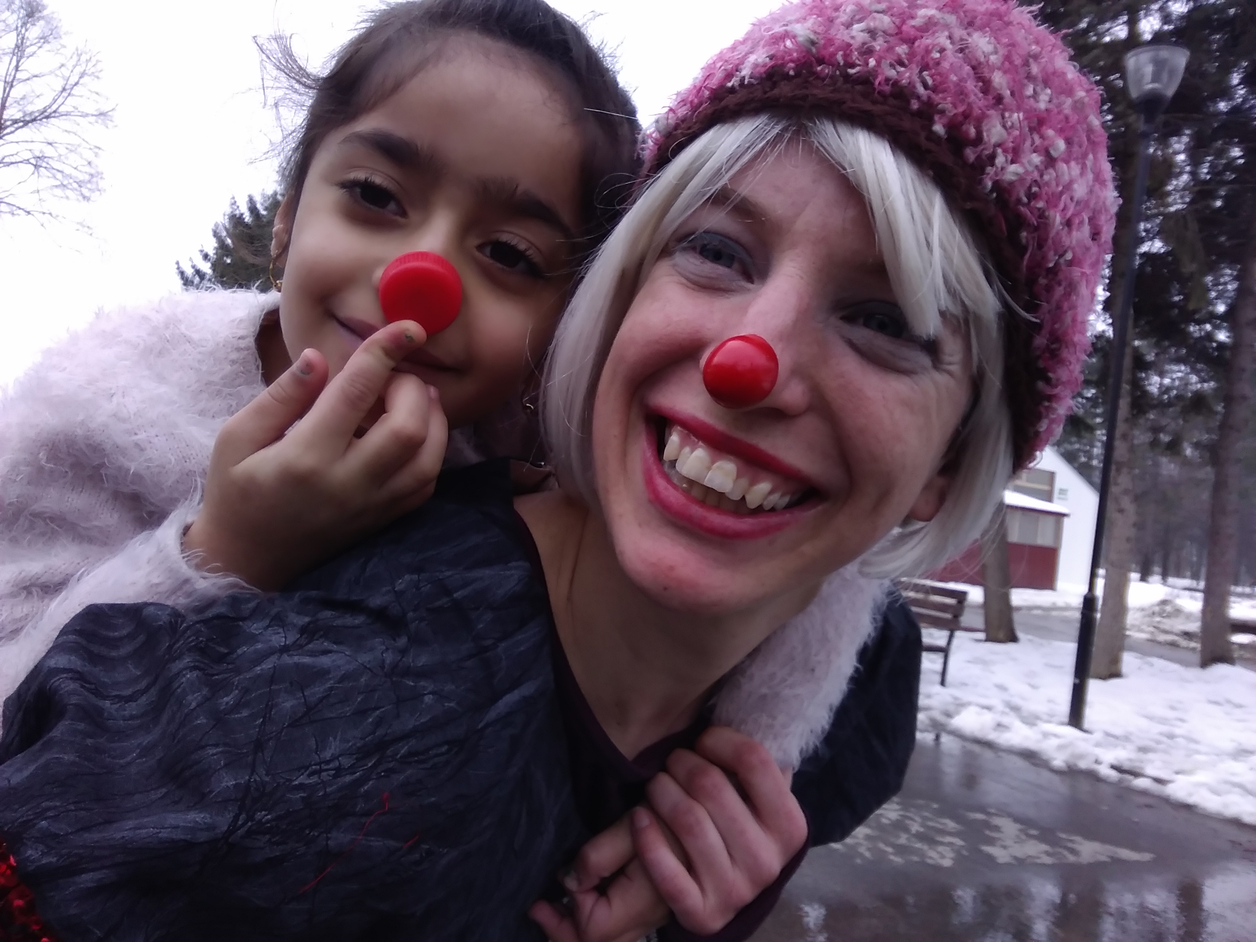Bekha and a little girl smile for the camera in their red noses