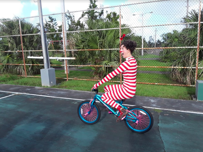 A clown rides a tiny bicycle