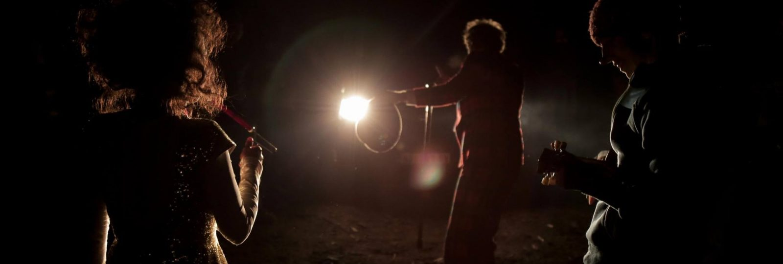 The clowns perform illuminated only by headlights