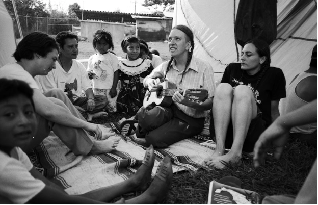 A clown plays guitar with a group of people in Chiapas