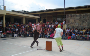 Clowns run in a circle around a suitcase, during a performance in Guatemala
