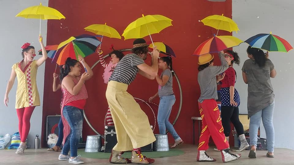 The group circles the stage with brightly colored umbrellas