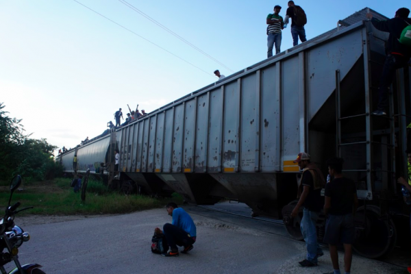 Paused train with migrants standing on top