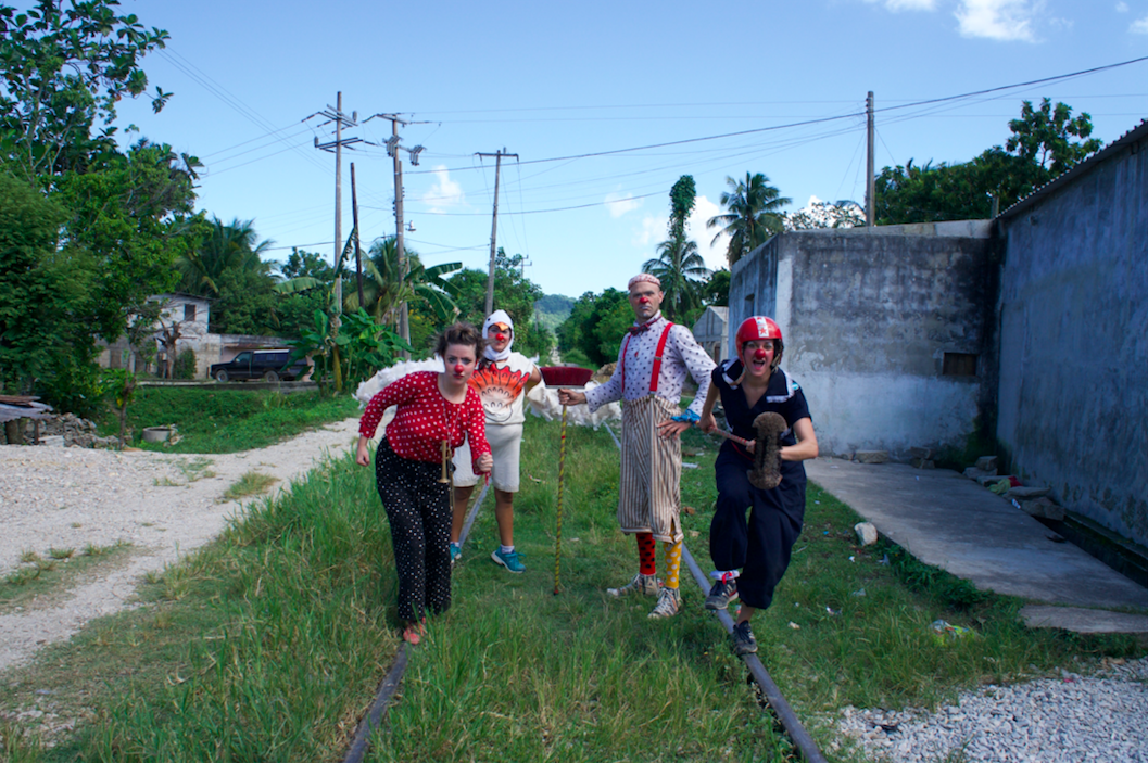 Clowns pose on grassy train tracks