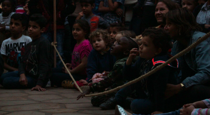 Kids sit behind the line watching a performance