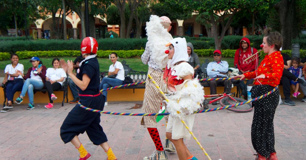 Clowns run in a circle inside a giant hula hoop