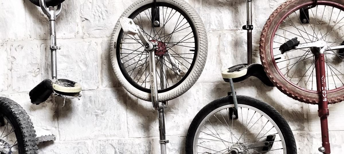 A handful of unicycles hang on a whitewashed cinderblock wall