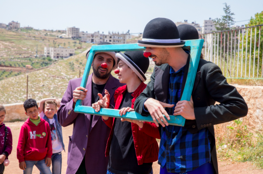 All the clowns squeeze inside a wooden picture frame. They are performing outside, in Palestine.