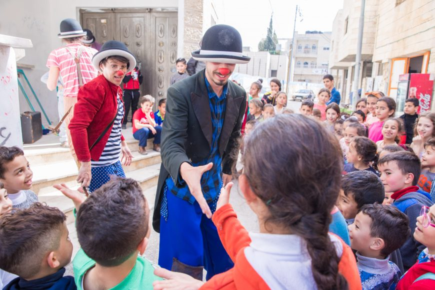 Ahmad wears a clown nose and a bowler hat, and reaches out to shake an audience member's hand