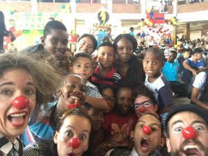 Lots of happy clowns and kids crowd forward to make silly faces at the camera.