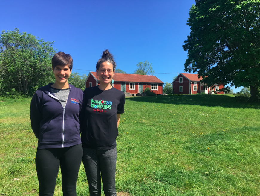 Naomi and Sarah smile at the camera as they stand on a green lawn