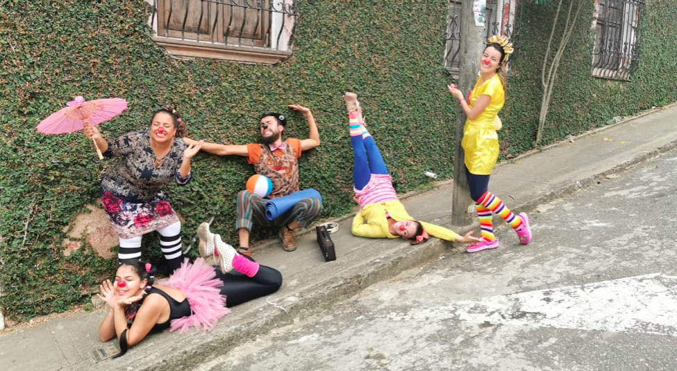 Five clowns make silly poses on a hill in Cali, Colombia