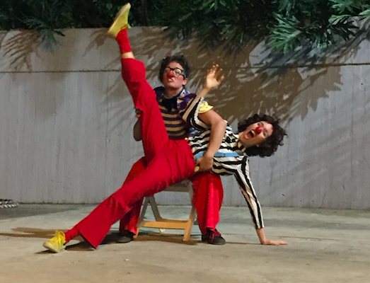 A female clown falls over toward her left hand, as she tries to sit on another female clown's lap.