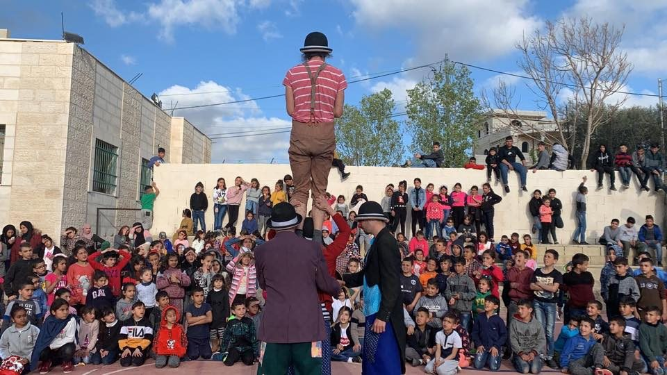 Poki balances on Ania's shoulders, in front of a large outdoor audience