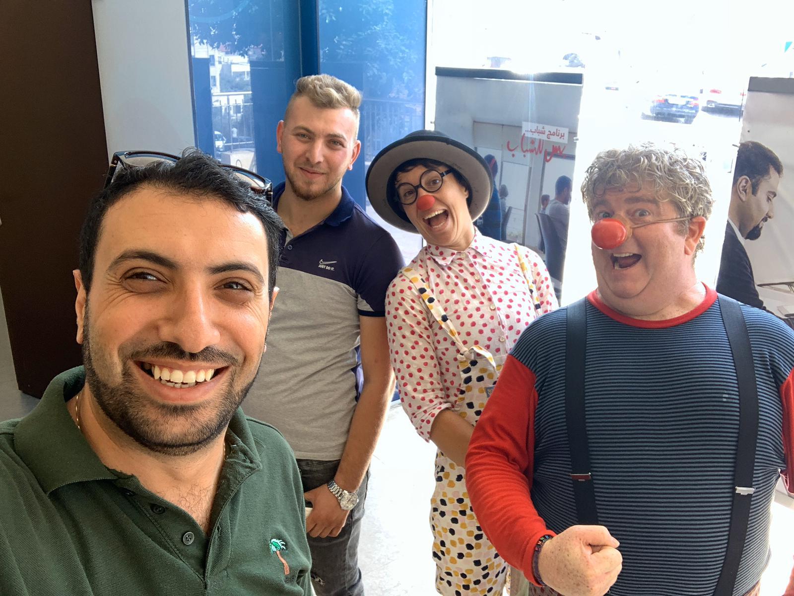 Osama, a stranger, Ania and Michael pose at the bank
