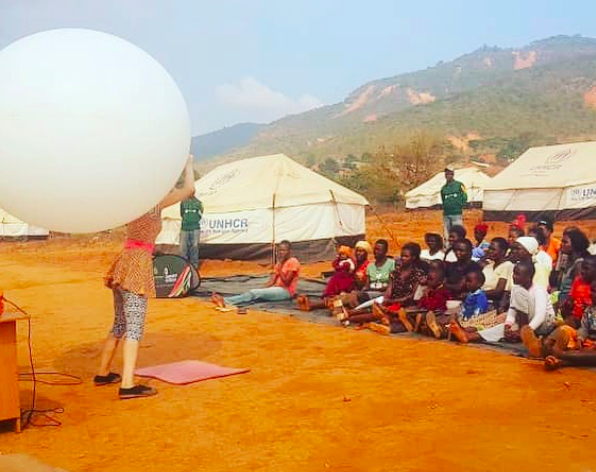 Robin Lara's head is inside a giant balloon as she performs in a rural refugee camp in Zimbabwe