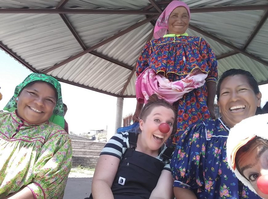 Three Rarámuri women in colorful dresses and headscarves smile at the camera. Two clowns, wearing red noses, make goofy faces.