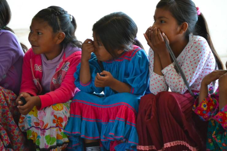 Three Rarámuri girls sit shoulder-to-shoulder as they watch a clown show